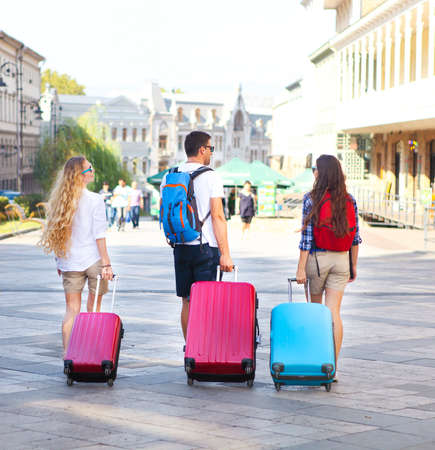 outwear: Travelers friends with luggage walking by street in the city. Selective focus Stock Photo