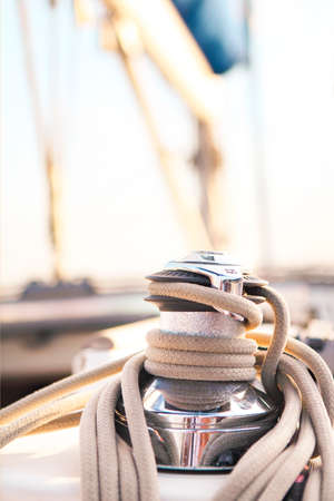 yachting: Sailboat detailed parts. Close up on winch and rope of yacht over blue sea. Yachting concept. Shallow depth of field