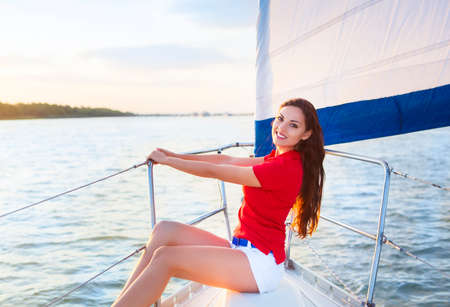 woman sunset: Attractive brunette girl on a yacht at summer day