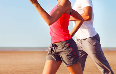 figure out: Couple jogging outside, runners training outdoors working out in nature against blue sky. Close up Stock Photo