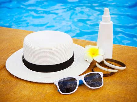 suncream: Suncream, sunglasses, hat, bracelet near the swimming pool. Vacation concept