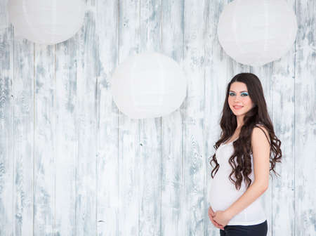 white woman: Portrait of beautiful smiling pregnant woman wearing casual jeans over wooden white background