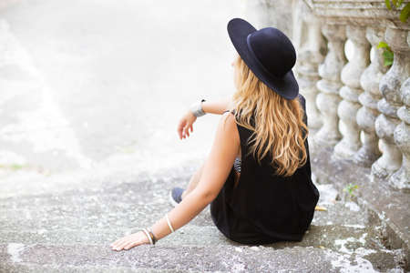 Beautiful hippie young woman wearing boho chic clothes and black hat outdoors