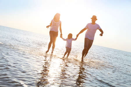 Happy young family having fun running on beach at sunset. Family traveling concept Foto de archivo