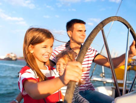 Young father with adorable daughters resting on a big boat