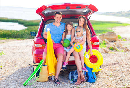Portrait of a smiling family with two children at beach by car. Holiday and travel concept 스톡 콘텐츠