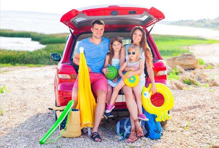 Portrait d'une famille souriante avec deux enfants à la plage en voiture. Vacances et le concept de Voyage