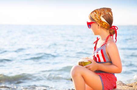 Wenig glücklich adorable Mädchen trinken Kokosmilch am Strand