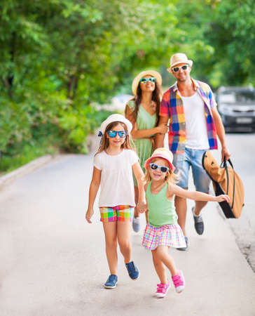 Glückliche junge Familie, die mit Gitarre Ausgaben unbeschwerte Zeit zusammen. Reisen und Urlaub Konzept Standard-Bild