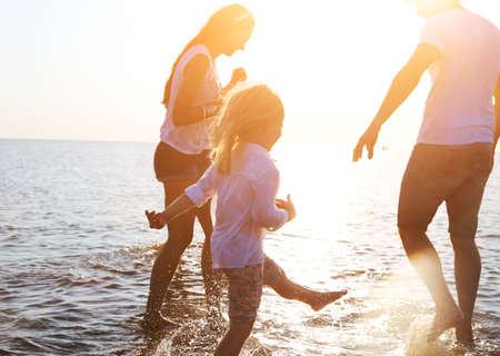 Happy young family having fun running on beach at sunset. Family traveling concept Stock Photo