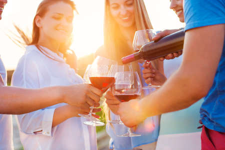 sun down: Group of happy friends having red wine on the beach. Sunset beach party