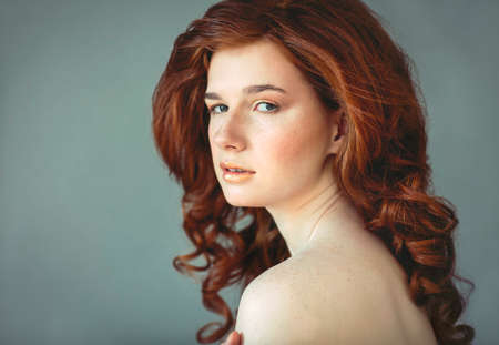 freckled: Beautiful young redhead woman with freckles portrait with curly hairdress