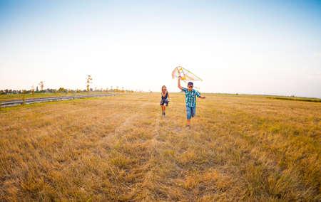 niños felices: Felices los niños pequeños que juegan con la cometa del vuelo en el campo de verano