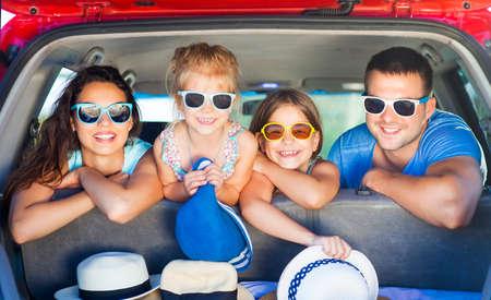 jovem: Retrato de uma família sorridente com duas crianças na praia no carro. Férias e conceito do curso