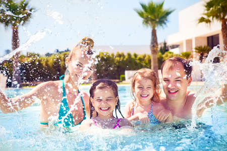 splash pool: Happy family with two kids having fun in the swimming pool. Summer vacation concept