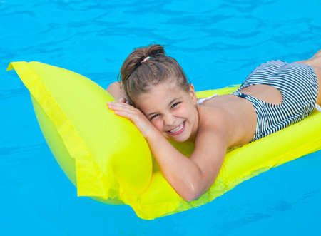 Happy little girl swimming on inflatable beach mattress
