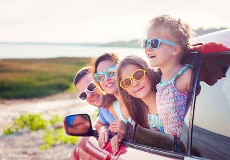 Portrait d'une famille souriante avec deux enfants à la plage dans la voiture. Vacances et le concept de Voyage Banque d'images - 57292338