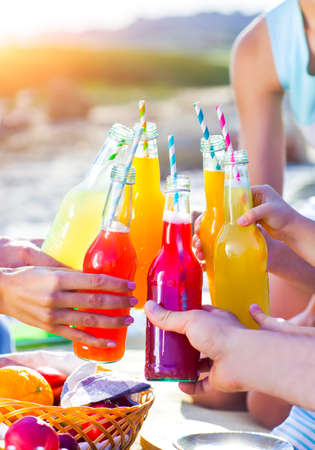 Group of friends holding drinks at the summer picnic. Close up