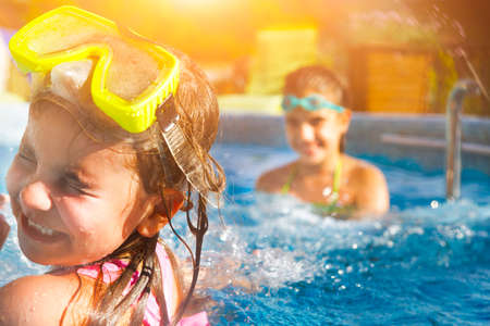 kiddies: Children playing in pool. Two little girls having fun in the pool. Summer holidays and vacation concept
