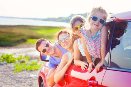 Portrait of a smiling family with two children at beach in the car. Holiday and travel concept Stock Photo - 59660435