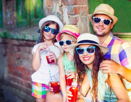 joven familia feliz en la calle con sombreros y gafas de sol. Vacaciones y el concepto de viaje