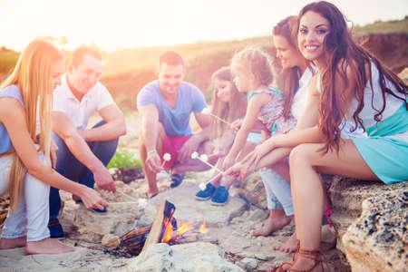 Amis assis sur le sable à la plage en cercle avec la guimauve sur la plage