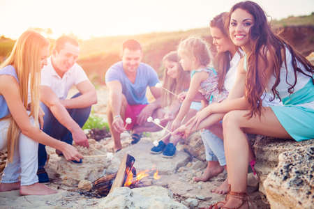 Friends sitting on the sand at the beach in circle with marshmallow on the beach Stock Photo