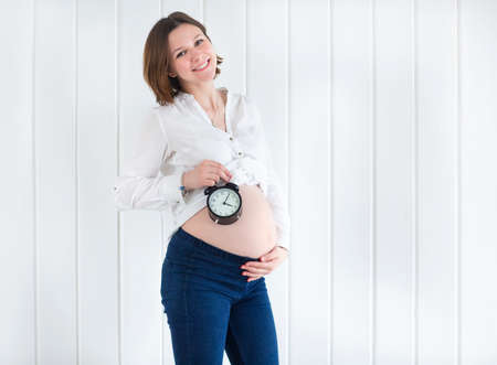 adult woman: Pregnant woman with a alarm clock in her hand