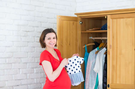 baby wardrobe: Young happy pregnant girl holding baby clothes near wardrobe Stock Photo