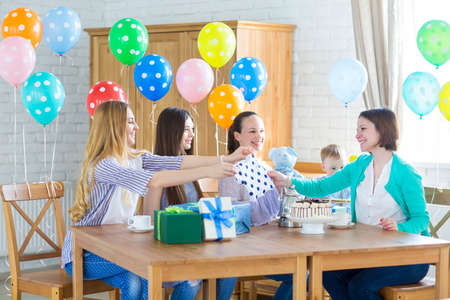 decorating: Portrait of pregnant woman with friends at a baby shower Stock Photo