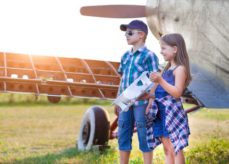 child model: Little boy and little girl pilot with handmade plane at the airport