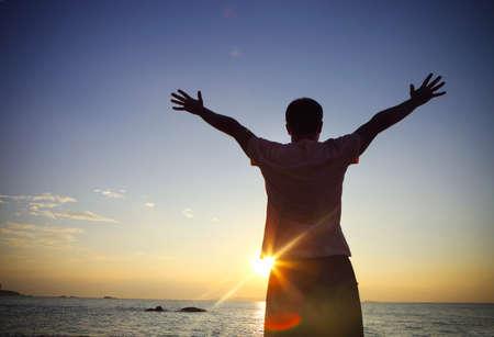 silueta hombre: Silueta de un hombre levantó las manos o los brazos abiertos en la playa al atardecer. concepto de la libertad Foto de archivo