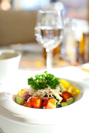 Fresh salad with tomatoes, cucumber, cheese and greens in the restaurant Stock Photo