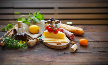 Italian food ingredients with olive oil on wooden background
