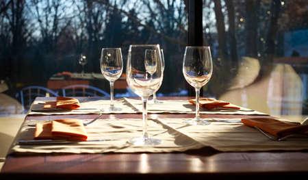 fork glasses: Glasses, fork, knife served for dinner in restaurant with cozy interior Stock Photo
