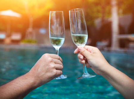 champagne glasses: Couple holding glasses of champagne making a toast by the pool
