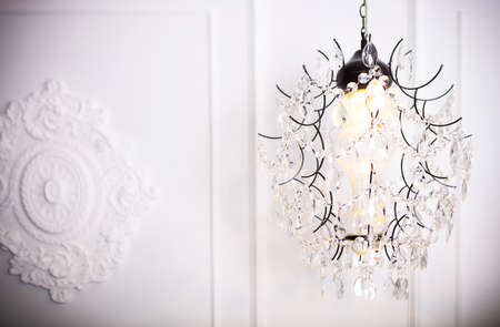 crystal chandelier: White glass chandelier on white background n classical interior. Glamour background with copy space
