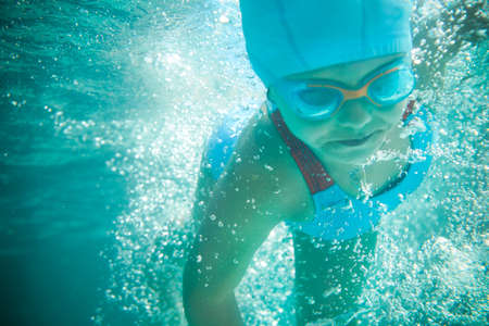 birretes: Niña en un traje de baño nada en la piscina bajo el agua Foto de archivo