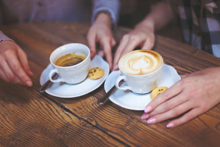 Female friends hands holding cups of coffee on rustic wooden table background Stock Photo
