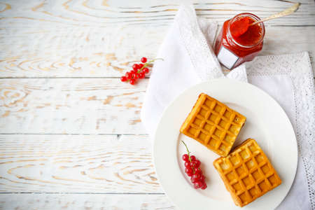 biscuit biscuits: Waffles with red currant jam and berries on a white plate on the wooden background Stock Photo