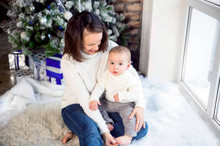 Happy mother with her baby boy siting near the Christmas tree Stock Photo