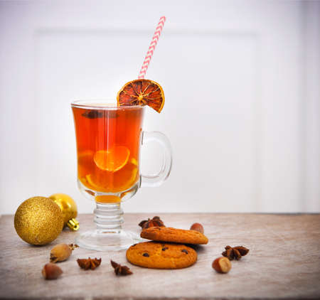punch spice: Hot winter tea with spices - cinnamon, cloves and star anise and cookies with nuts on a light wooden background