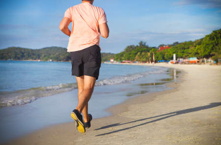 Young man running on the beach at sunrise