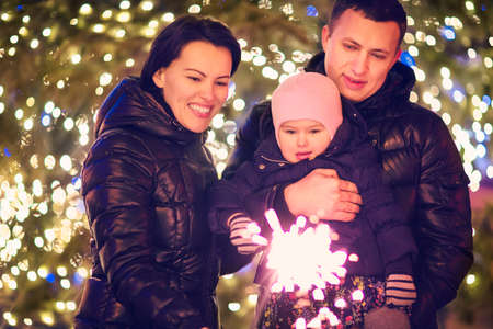 family outside: Happy family with Bengal light outside over Christmas background Stock Photo
