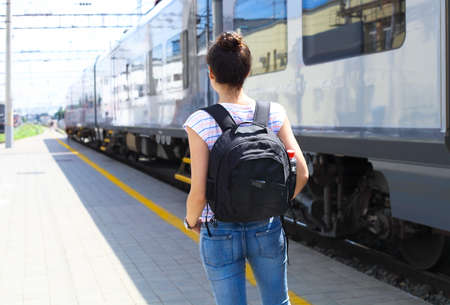 Travel concept. Young woman with backpack on train station. Rear view. Stock Photo
