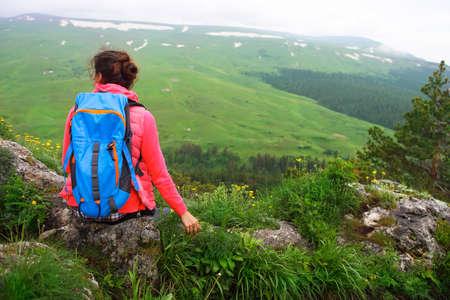 mochila de viaje: Caminante con el morral relajante en la cima de una montaña y disfruta de la opinión del valle, durante la salida del sol