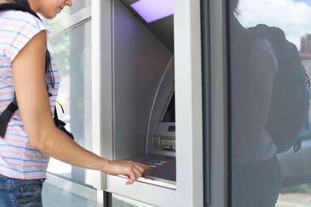 bankomat: Young tourist woman using banking machine outdors Stock Photo