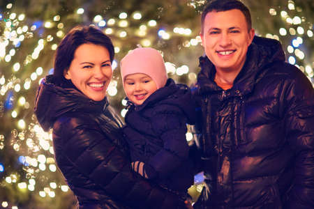 family outside: Happy family with little daughter looking at camera outside over Christmas background Stock Photo