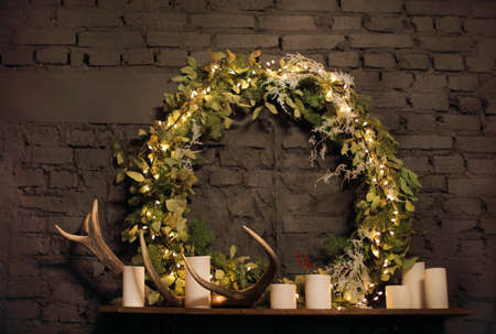 mantel: Christmas wreath above mantel on brick wall background with lights, candles and deer antler Stock Photo