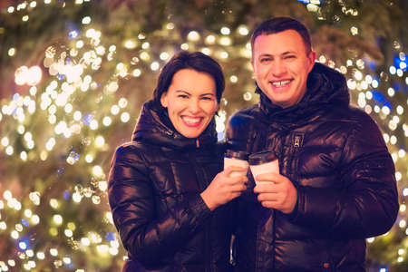 couple outdoor: Happy couple drinking hot beverages at winter holidays Stock Photo